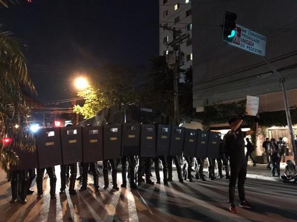 Policiais com escudos no Largo da Batata, em frente a manifestante segurando cartaz