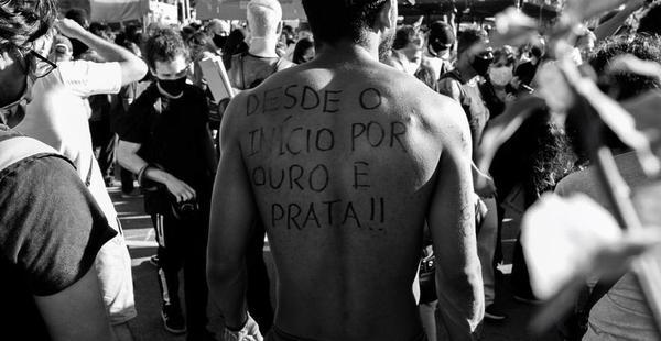 Manifestante em multidão tem suas costas pintadas com os escritos