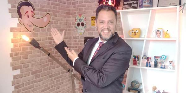 Gilmar Lopes mostra o logo do E-farsas, em frente a uma estante de brinquedos