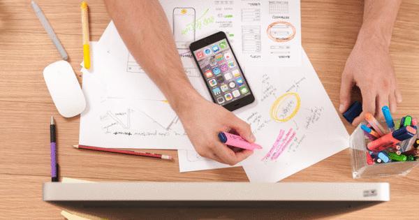 Trabalho em mesa, com papéis, celular e materiais de papelaria