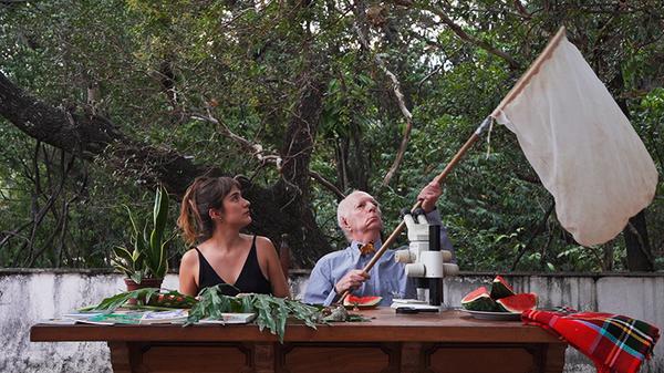 Mariana Machado e Ângelo Machado sentam diante de uma mesa cheia de objetos