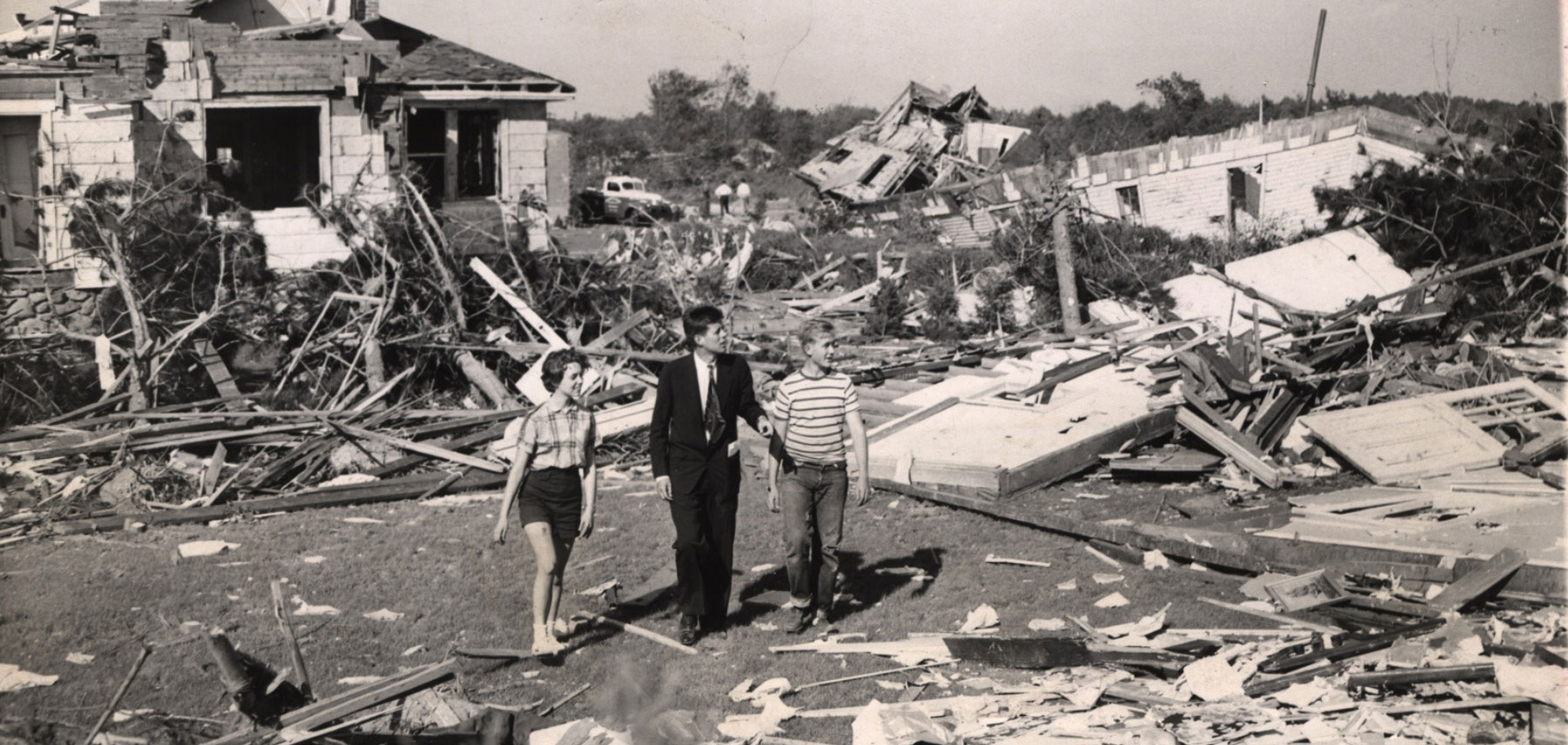 Photo of young Massachusetts Senator John F. Kennedy surveying the damage in Worcester.