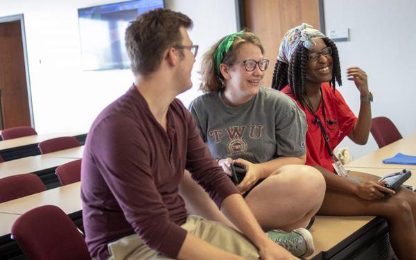 Members of TWU's Smash Brother's Alliance sit on top of a table in a repurposed classroom during the Smash Social social gaming event held at TWU.