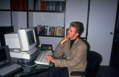 Rock star David Bowie working on desktop computer in office. © Time Inc.
