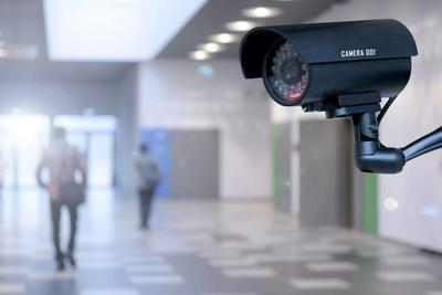 A large hallway with a security camera in the foreground. The background is blurred and there are two people walking away.
