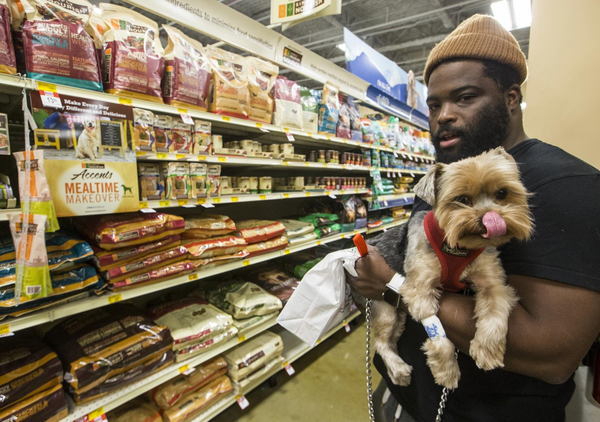 Tron Oliver holds Rocket, his Yorkshire terrier, in the dog food aisle of a PetSmart store in Los Angeles. [The Associated Press file photo]