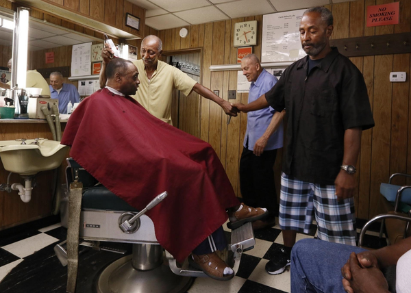 Paul Locke, center, watches Bob Dillard cut customer Grady Harris' hair while Dillard shakes hands with fellow barber Richard Blue, who works down the street and stopped by to wish Locke and Dillard a happy retirement. The pair closed their show on June 28. [Eric Albrecht/ Dispatch]