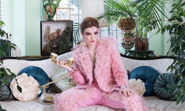 Fashion designer Sophie Cochevelou sitting on a couch wearing a pink suit - interview