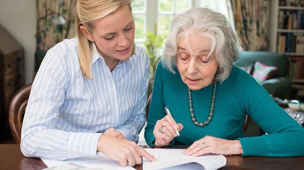 Elderly lady signing document
